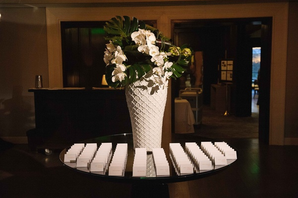 Escort card table white vase with jungle leaves and orchids Brentwood Country Club Carol Leifer