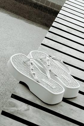 White platform flip flops with rosettes on straps
