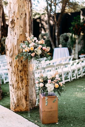 wedding ceremony tall tree with lucite riser holding peach pink flower arrangement greenery