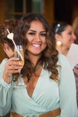 Wedding shower guest in mint dress, brown belt with Champagne flute, pink & white straw, gold heart