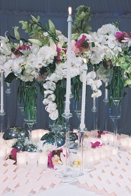 Escort card table with lily and orchid flowers in tropical colors