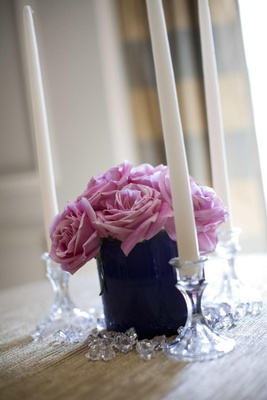 Small arrangement of light purple flowers surrounded by three taper candles in crystal holders