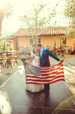 Jenna Reeves and Tim Lopez hold American flag on dance floor of their Santa Barbara wedding 4th