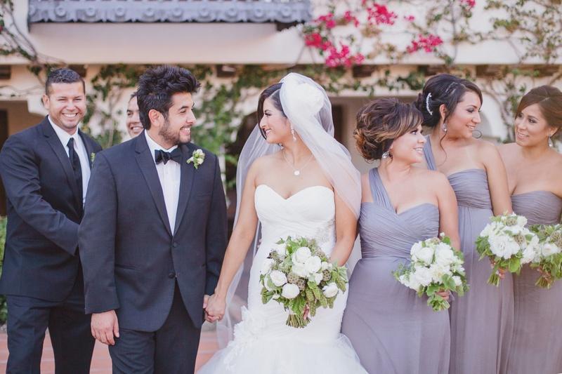 Purple bridesmaids and tuxedo groomsmen with couple