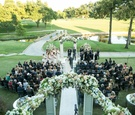 Bride and father walk down aisle with guests at country club golf course in Dallas