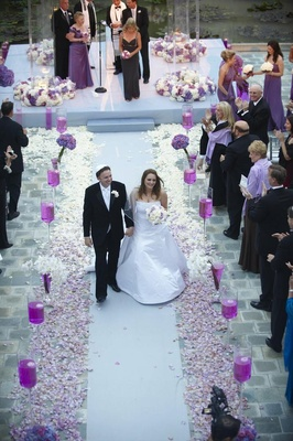 Bride and groom walk up white aisle with purple flowers