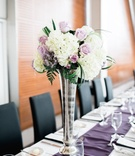 Long rectangle wedding table with purple runner silver vase white hydrangea purple rose and greenery