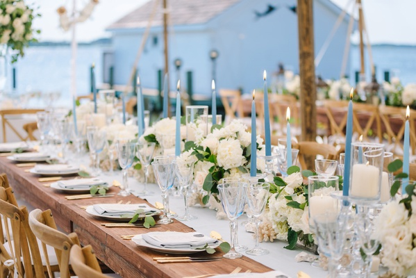 blue tapered candles interspersed amongst collection of ivory florals