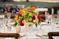 Rose gold flatware and glassware rims low centerpiece orange green red pink yellow flowers wood