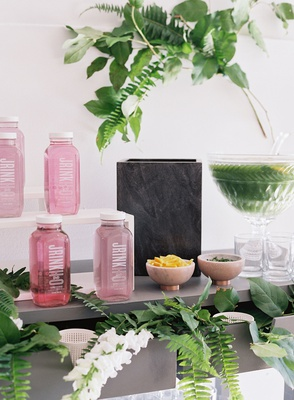 Cold-pressed juice jrink pink drink in bottles punch in crystal tray on bar cart ferns greenery