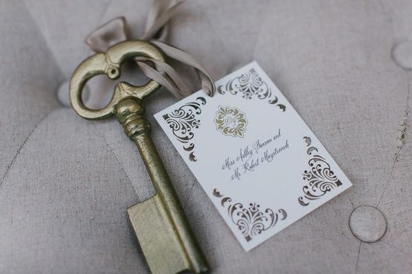 Ceci New York place card with damask print tied to antique golden key with ribbon