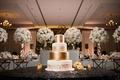 Four layer wedding cake white and gold layers with large initial cake topper drip and design detail