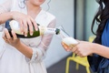 Bride in white robe getting ready pouring champagne bottle into bridesmaid glass
