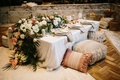 wedding reception or bridal shower engagement party idea low table pillow pouf flower runner