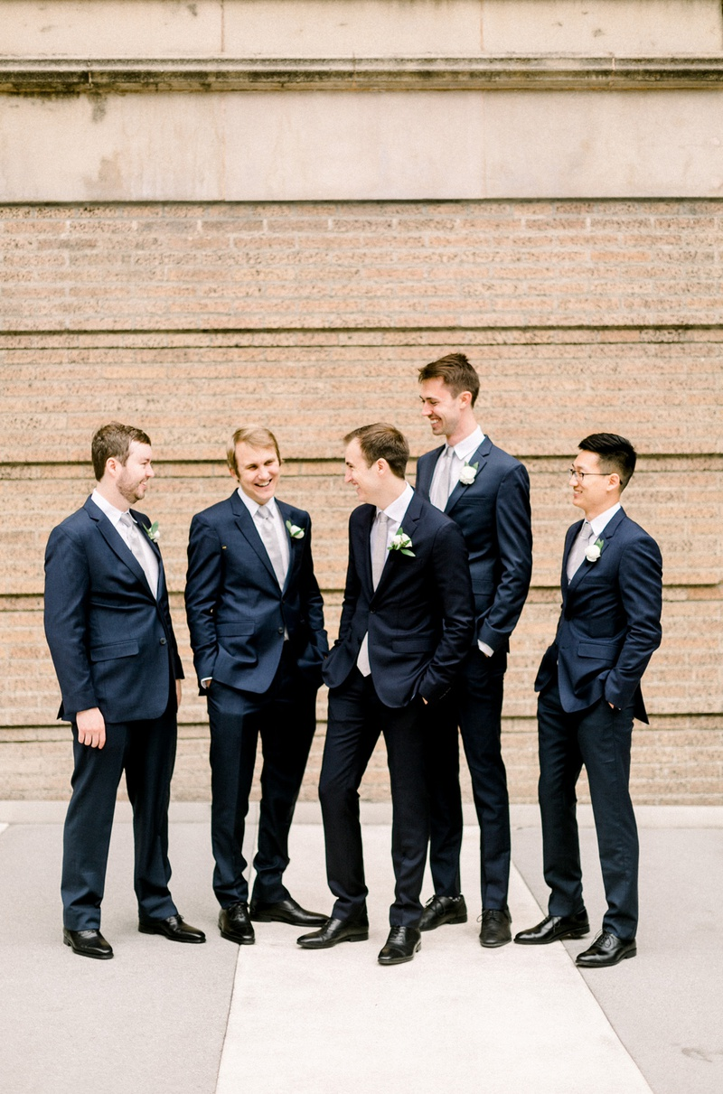 groom and groomsmen in navy suits and black dress shoes casually hanging out