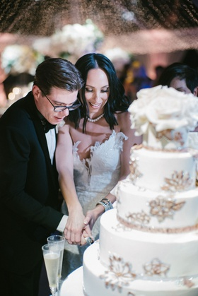 cheryl burke and matthew lawrence cutting into wedding cake bride in second dress white gold cake