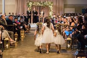 three flower girls in white dressed walk down aisle jewish wedding
