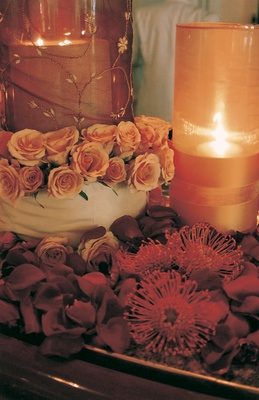 Red rose petals and golden candles