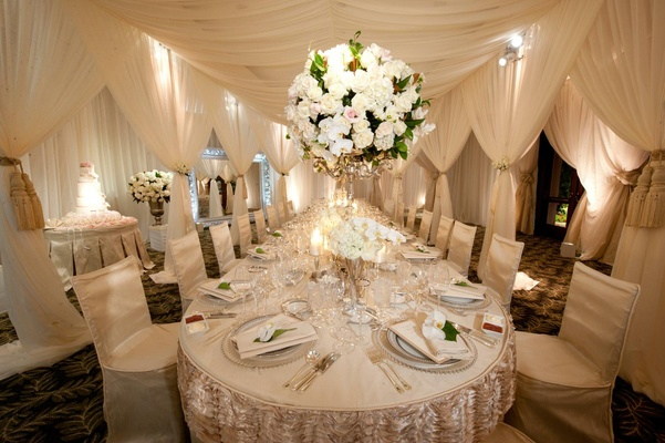 Long reception table under white canopy with large flower arrangement