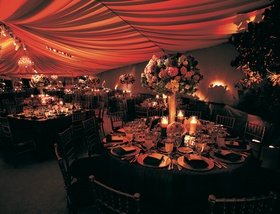 Wedding reception table decorated with a tall arrangement of red, purple, green, and white flowers