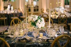 wedding reception round table short centerpiece tall taper candles navy blue linens gold rim charger