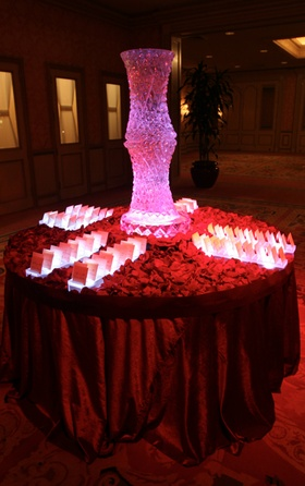 Wedding reception place card table covered with red rose petals and topped with a vase ice sculpture