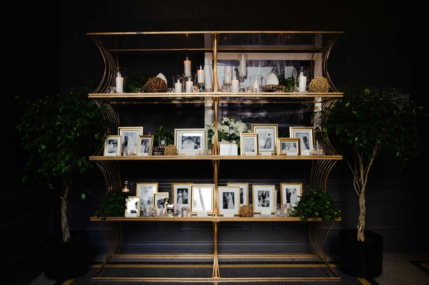 wedding reception gold bookcase bookshelf black and white family photos on bookcase