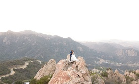 Wedding photo bride and groom on rock hill mountain overlooking Malibu canyon views malibu rocky oak