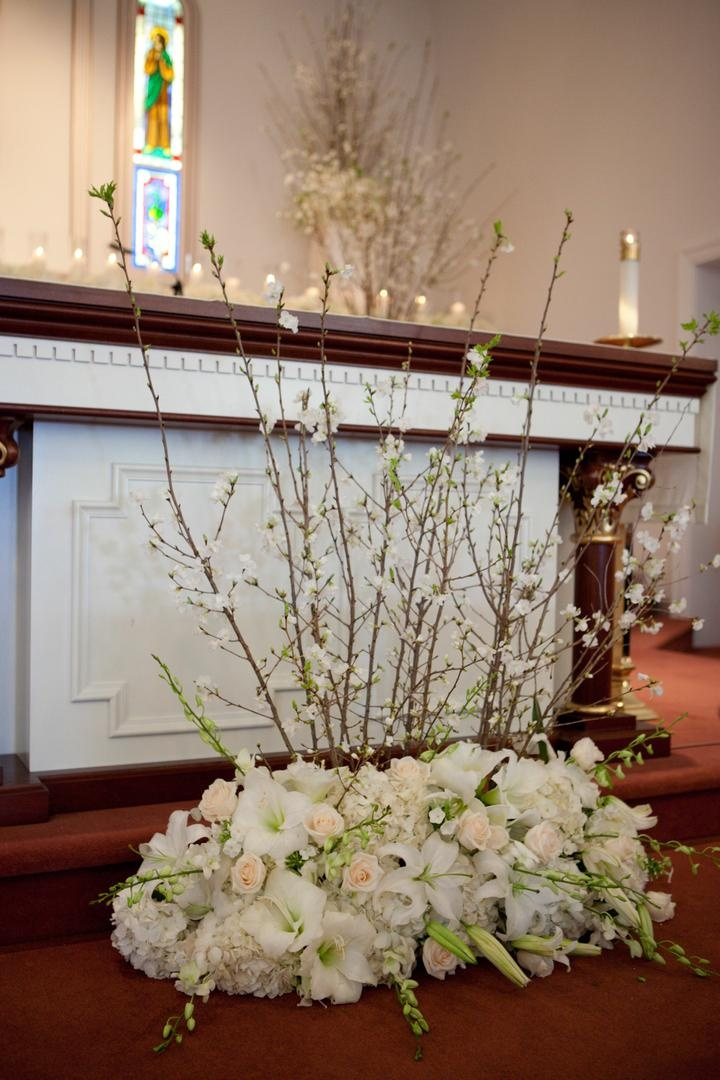 Altar decorated with light colored flowers and cherry blossom branches for a wedding