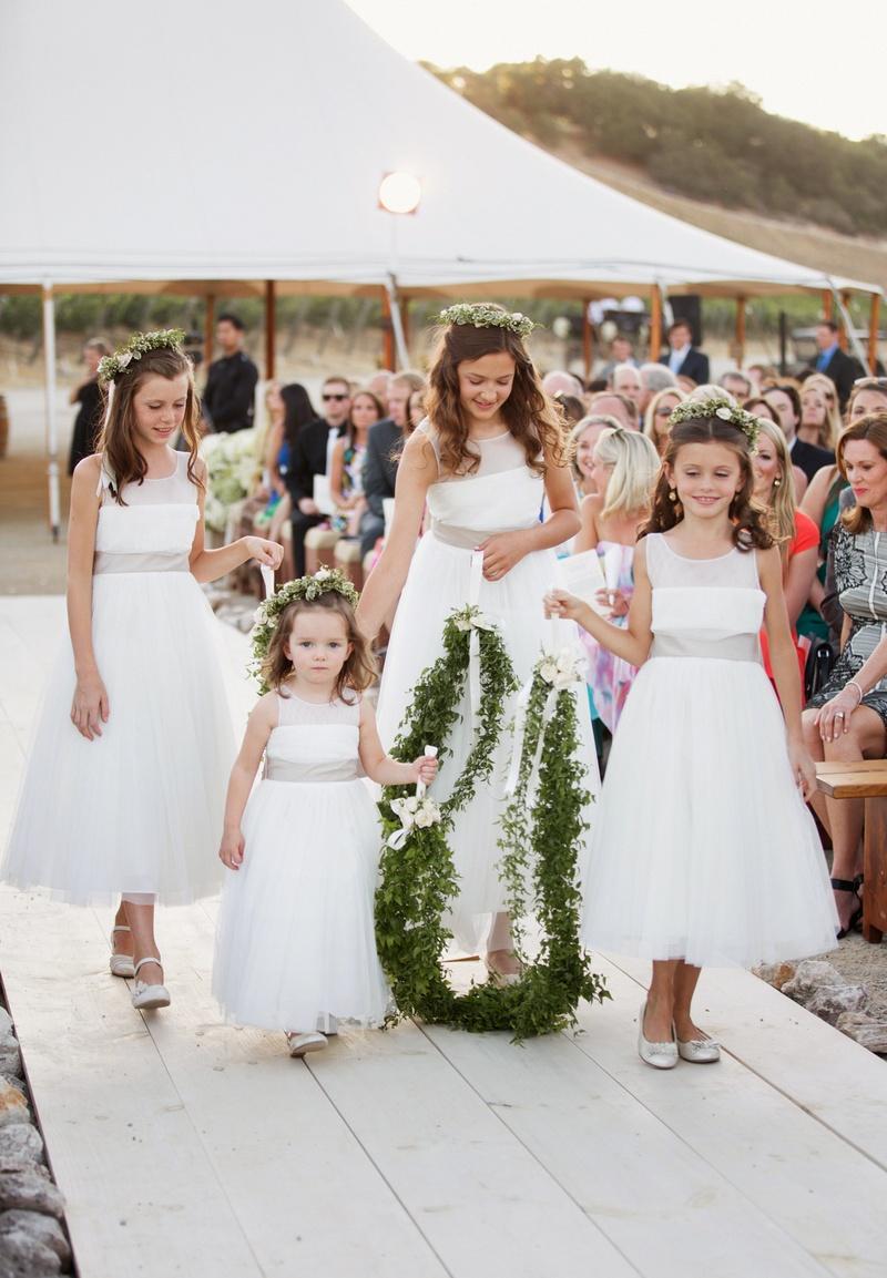 Four flower girls walk down aisle holding garland