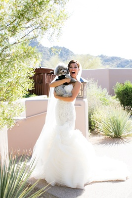 Adrianna Costa in bridal gown holding grey poodle