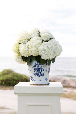 Ivory riser with blue and white compote vase with fluffy white hydrangea flowers