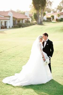 bride in carolina herrera ball gown in veil with groom in custom dolce&gabbana tux on lawn