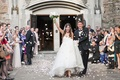 friends and family throw flower petals at the newlyweds as they leave their church ceremony