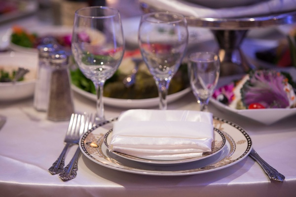Shimmering satin napkin on top of black and gold china with antique inspired fork knife spoon