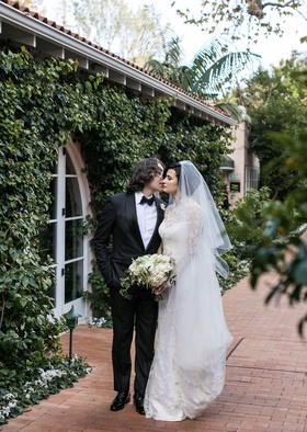 Wedding portrait bride in veil and long sleeve wedding dress groom tuxedo bow tie kisses cheek