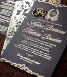Wedding invitation with wedding rings and band on top black stationery gold lettering and monogram