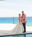 oceanside wedding portrait, bride in mark zunino, groom in salmon tuxedo jacket
