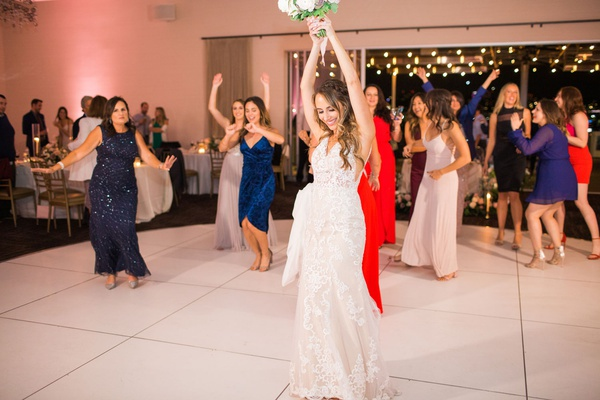 bride in lace stella york gown about to throw bouquet to female guests