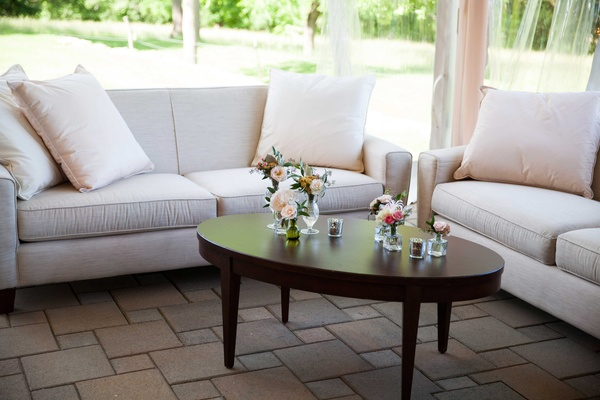 comfortable lounge area with white couches and simplistic detailing in outside tented space