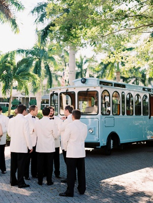 Groomsmen in white tuxedo jackets standing by light blue trolley car for wedding ceremony transport