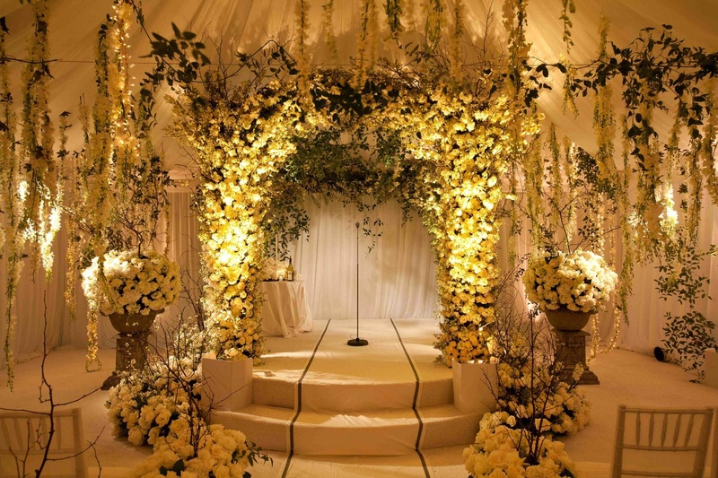 indoor wedding arches. indoor garden ceremony with white roses and orchids greenery wedding arches