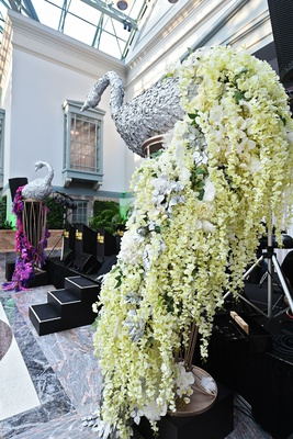 wedding reception decoration silver peacock with tail train white orchid silver leaves pink purple