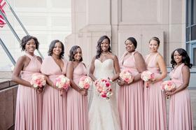 bride in strapless wedding dress curled hair necklace bridesmaids in mismatch neckline pink dresses