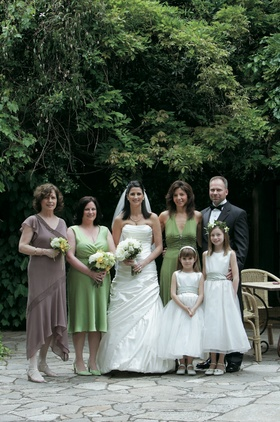 Bride in a Pnina Tornai gown and groom in a black tuxedo with bridal party members