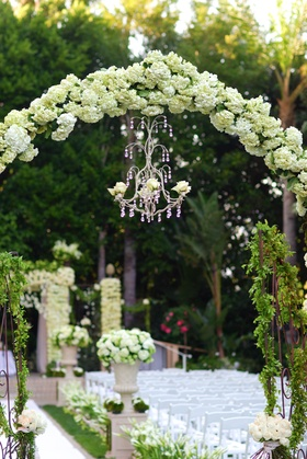Grassy ceremony with hundreds of white flower arrangements and a chandelier