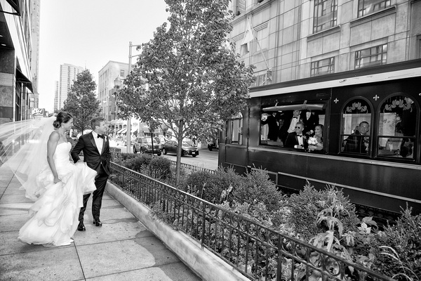black and white photo of bride and groom looking at bridal party in a trolley
