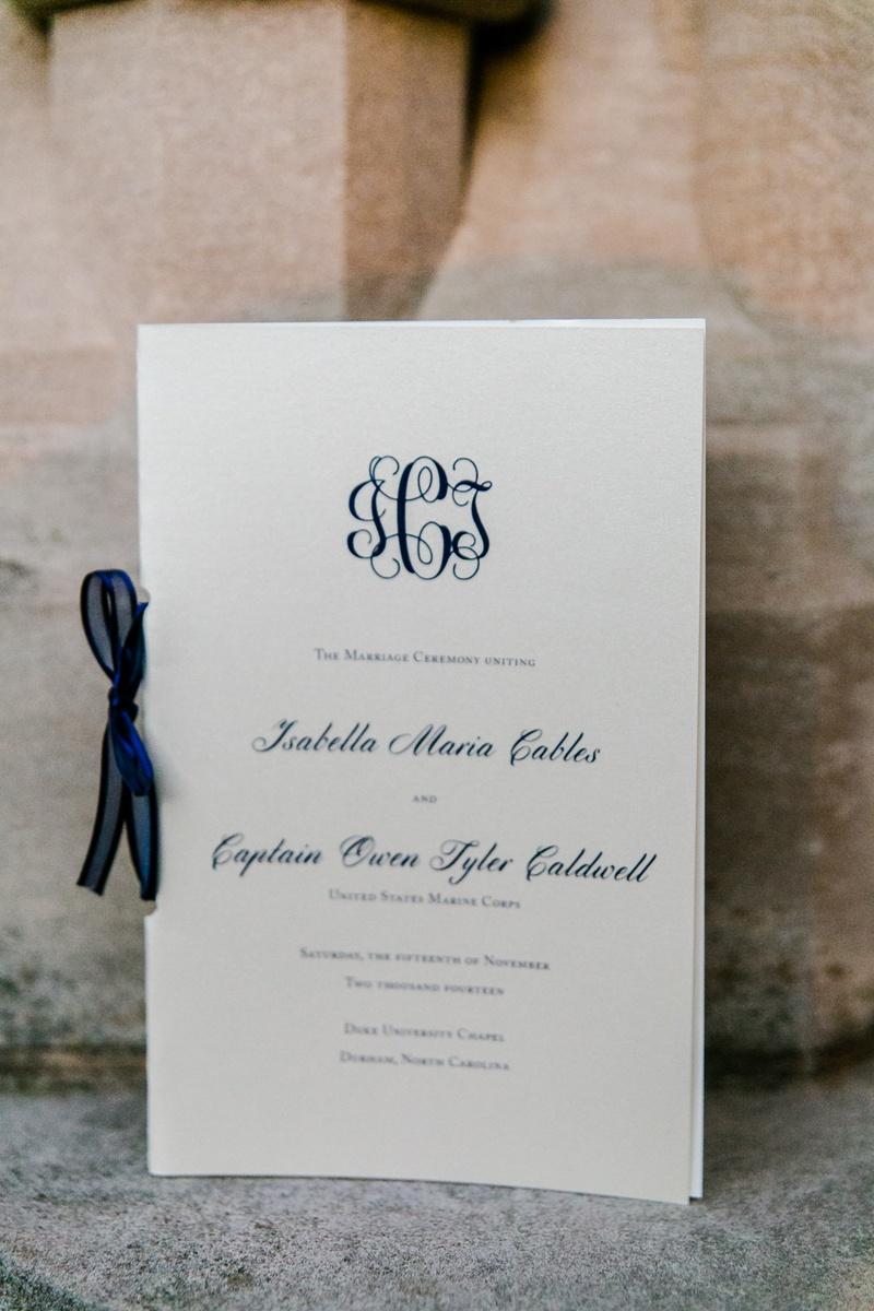 White wedding program with blue ribbon and monogram