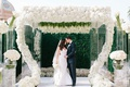 Bride and groom wedding portrait hedge wall white flower swirling chuppah lucite column white flower