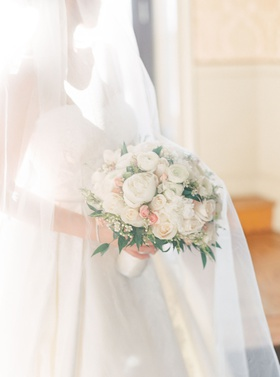 bride wearing white gown with long veil over rounded bouquet of white pink flowers ranunculuses rose